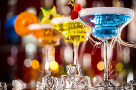 nightclub bar: Martini drinks served on bar counter with blur bottles on background