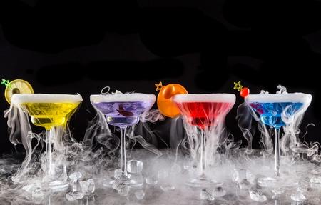 frutas secas: Bebidas Martini con efecto de humo de hielo seco, que se presentan en barra de bar con fondo negro