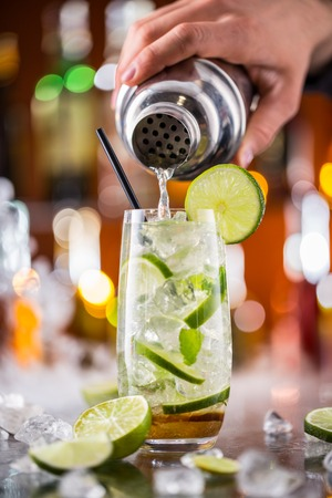 cocktail shaker: Mojito cocktail drink on bar counter with barman holding shaker on background