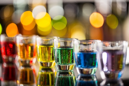 nightclub bar: Variation of hard alcoholic shots served on bar counter. Blur bottles on background