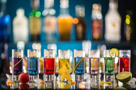 horizontal bar: Variation of hard alcoholic shots served on bar counter. Blur bottles on background