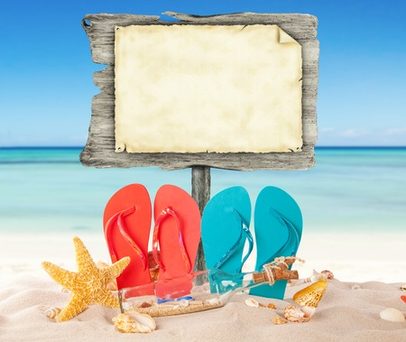 Summer beach with colored sandals and blank wooden poster. Blur azure sea on background Stok Fotoğraf