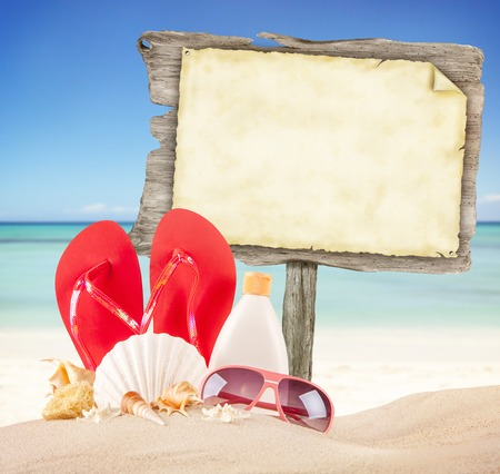 Summer beach with accessories and blank wooden poster. Blur azure sea on background