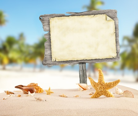 beach: Summer beach with shells, stars and blank wooden poster. Blur azure sea on background