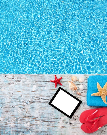 Top view of summer accessories and blank tablet on wooden planks placed next to swimming pool