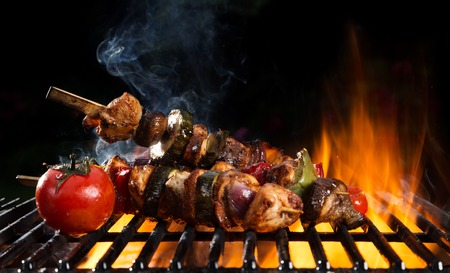 shishkabab: Fresh skewer on grill with flames. Isolated on black background
