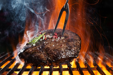 Beef steak on grill, isolated on black background