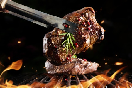 carne asada: Filete en parrilla, aislado en el fondo negro