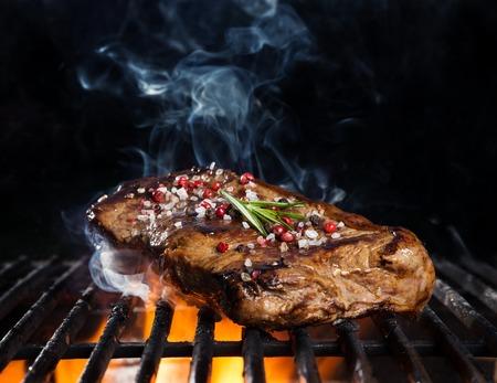 Rindersteak auf dem Grill, auf schwarzem Hintergrund isoliert Standard-Bild - 40284957