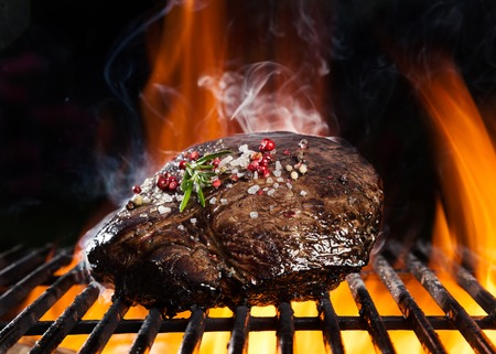 barbecue fire: Beef steak on grill, isolated on black background