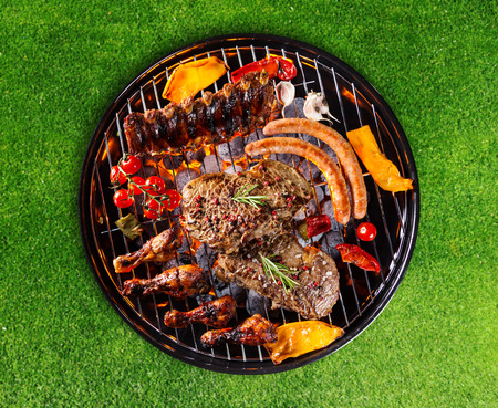 select: Barbecue grill with various kinds of meat. Placed on grass