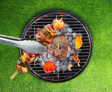barbecue ribs: Barbecue grill with various kinds of meat. Placed on grass