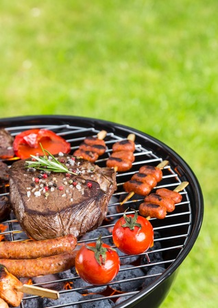 kinds: Barbecue grill with various kinds of meat. Placed on grass