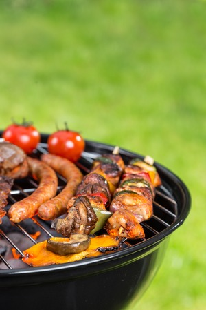 bbq: Barbecue grill with various kinds of meat. Placed on grass