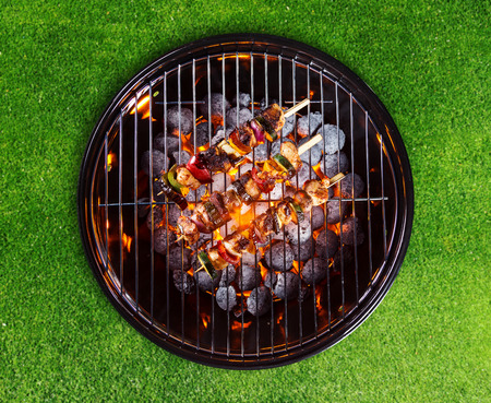 bbq grill: Barbecue grill with skewers. Placed on grass