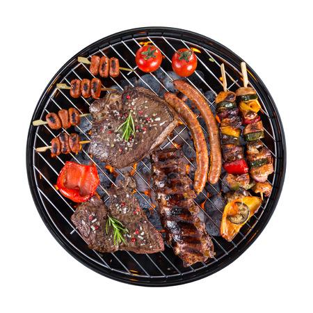 chorizos asados: Barbacoa exterior con carne y verduras, aislado en fondo blanco Foto de archivo
