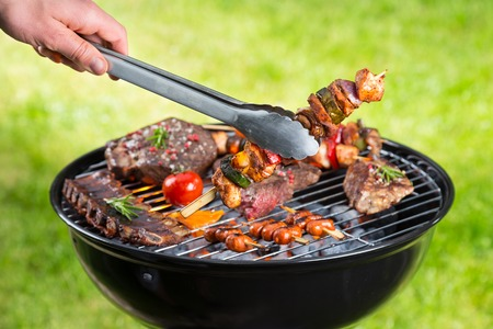 meat skewers: Barbecue grill with various kinds of meat. Placed on grass.