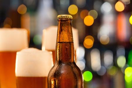 cerveza: Botella de cerveza con jarras de desenfoque en el fondo