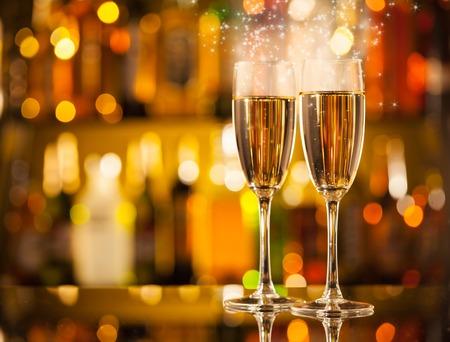 Viering thema met twee glazen champagne. Onscherpte flessen op de achtergrond