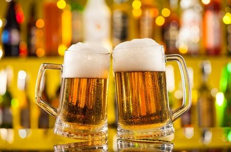 saúde: Jarras de cerveja colocado no balcão de bar com copyspace Banco de Imagens