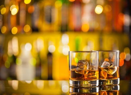 bebidas frias: Bebidas whisky en barra de bar con botles desenfoque en backgorund