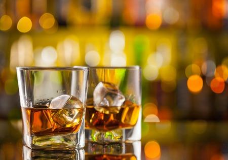 Whisky drankjes op bar met onscherpte botles op backgorund Stockfoto