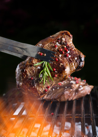 background black: Beef steak on grill, isolated on black background