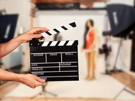 Man hands holding film clapper. Blur film studio on background 스톡 콘텐츠