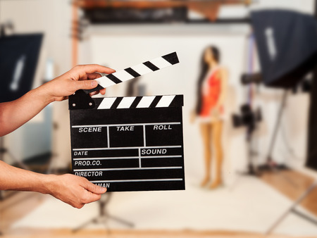 hollywood movie: Man hands holding film clapper. Blur film studio on background Stock Photo