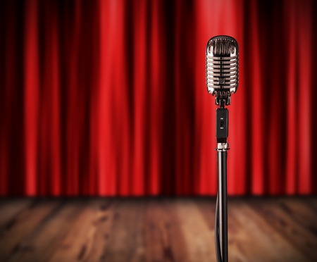 Retro microphone with red curtain and wooden stage on background