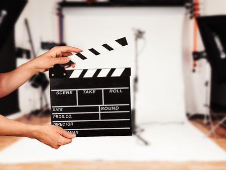 Man hands holding film clapper. Blur film studio on background Archivio Fotografico