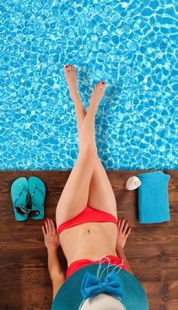 Young woman relaxing at swimming pool, sitting on wooden planks