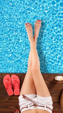 piernas mujer: Piernas delgadas de la mujer sobre la superficie piscina