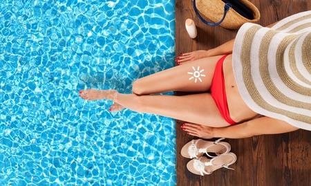 Junge Frau Entspannung und Sonnenbaden am Pool, sitzen auf hölzernen Planken