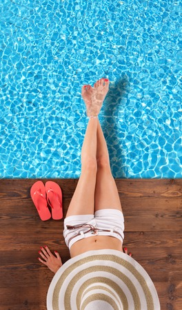woman sandals: Young woman relaxing at swimming pool, sitting on wooden planks