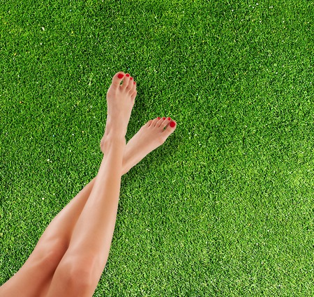 red grass: Perfect female legs placed above grass