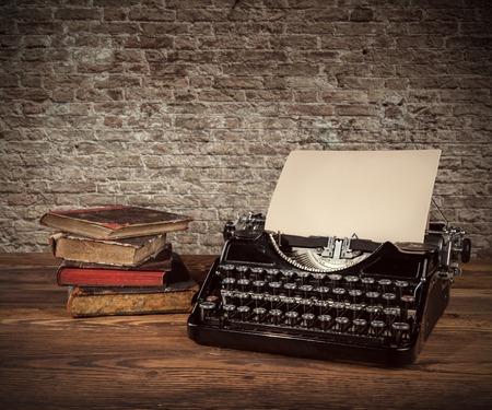 libros antiguos: Máquina de escribir retro colocado en tablones de madera. Pared de ladrillo vieja como fondo con copyspace.