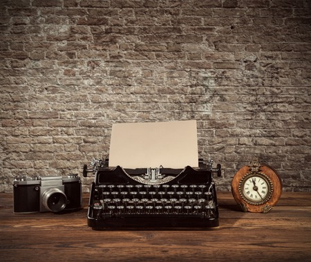 retro revival: Retro typewriter, alarm-clock and camera placed on wooden planks. Old brick wall as background with copyspace. Stock Photo