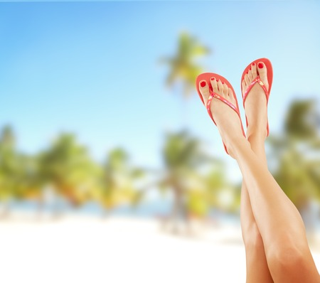 Perfect female legs on sandy beach with sandals Reklamní fotografie - 41649778