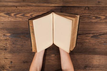 manos abiertas: Manos de mujer sosteniendo en blanco viejo libro en tablones de madera