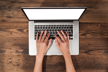 write: Aerial view of woman typing on laptop. Placed on wooden desk Stock Photo