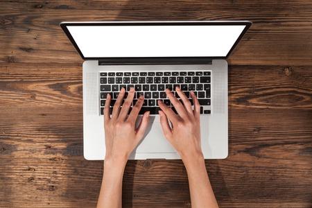 Vista aérea da mulher digitando no laptop. Colocado na mesa de madeira Imagens