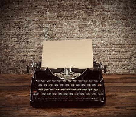 typewriter: Máquina de escribir retro colocado en tablones de madera. Pared de ladrillo vieja como fondo con copyspace.