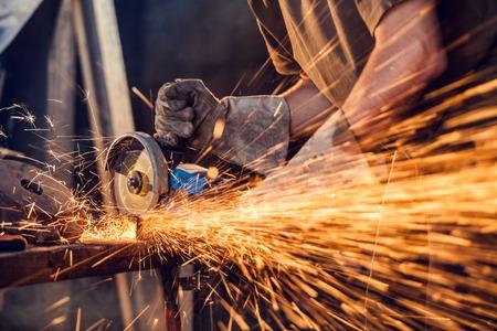 Close-up van de werknemer snijden metaal met molen. Vonken tijdens het slijpen ijzer. Lage diepte van de focus