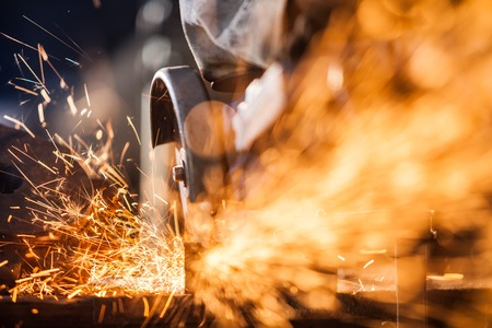 Close-up of worker cutting metal with grinder. Sparks while grinding iron. Low depth of focus Stock Photo