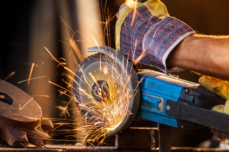 grinder: Close-up of worker cutting metal with grinder. Sparks while grinding iron. Low depth of focus Stock Photo