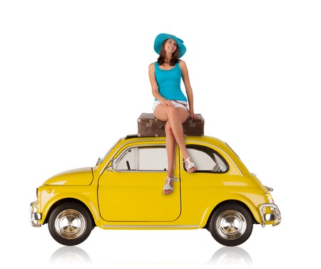 Beautiful young woman posing on old car, manufactured between year 1957 - 1975. Concept of summer travel. Isolated on white background Stock Photo