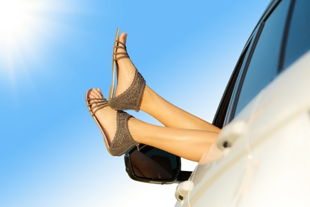 青空: Summer road trip car vacation concept. Woman legs out the windows in car. Conceptual freedom, travel and holidays image with copy space.