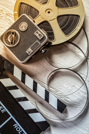 Film camera chalkboard, vintage camera and roll on wooden table Stock Photo