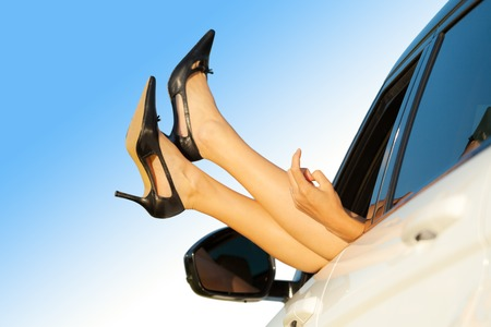 female sex: Summer road trip car vacation concept. Woman showing her legs and finger out of car. Conceptual photo of woman flirt